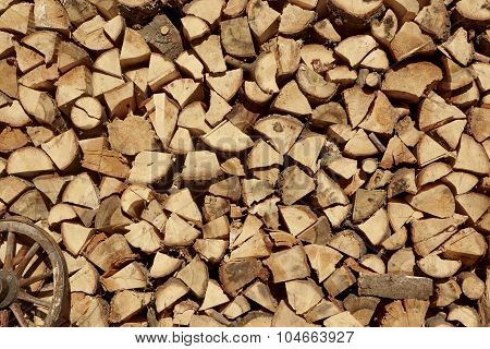 Large Woodpile From Chopped Firewood And Old Cart Wheel Background