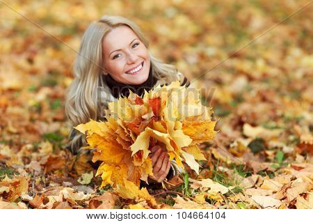 Woman with bunch of autumn orange maple leaves