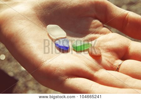 Color Glass in a Girl Hand on the Beach