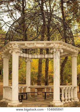 Classical rotunda with white columns in autumn park