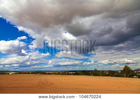 Plowed field, cloudy sky