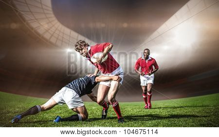 Rugby stadium against rugby players tackling during game