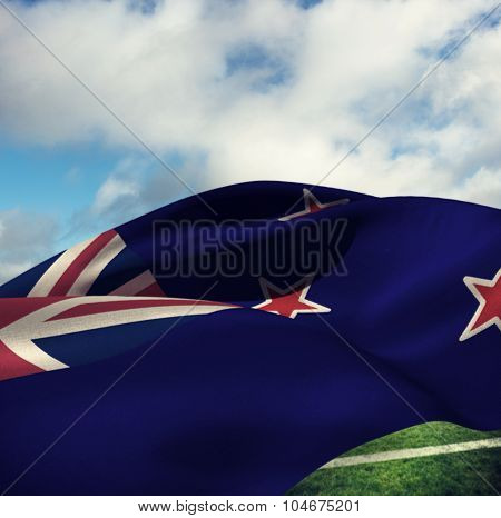 Waving flag of New Zealand against blue sky with clouds