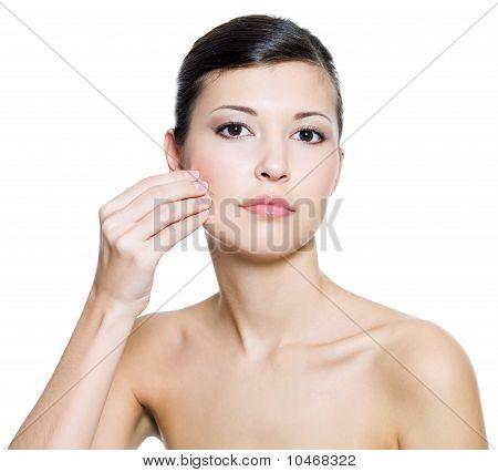 Tocar la piel de la mejilla de la mujer