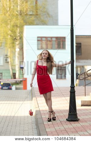 The girl in the red dress in front of a lamppost