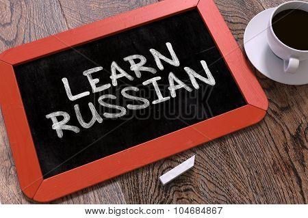 Learn Russian Handwritten by white Chalk on a Blackboard.