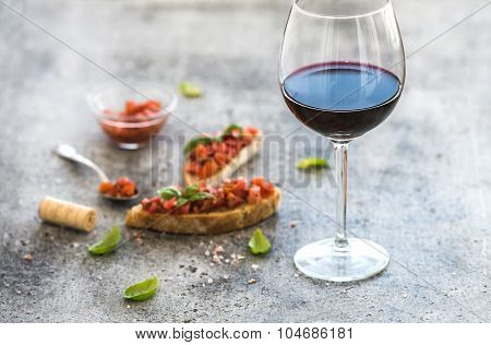 Wine appetizer set. Glass of red wine, brushettas with fresh tomato and basil on over rustic grunge