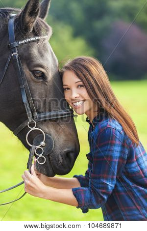 Beautiful happy Asian Eurasian young woman or girl wearing plaid checked shirt, smiling and resting her head on her horse in sunshine