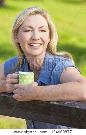 Beautiful happy middle aged woman in her thirties or forties smiling and leaning on fence in sunshine drinking tea or coffee