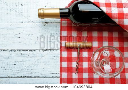 Bottle of wine, glass and corkscrew on wooden table