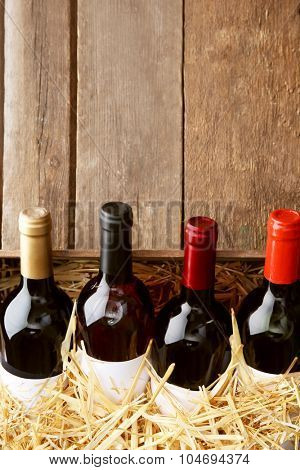 Box with straw and wine bottles on wooden background