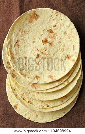 Stack of homemade whole wheat flour tortilla on brown napkin background