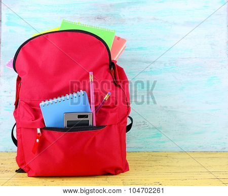 Red bag with school equipment on wooden background