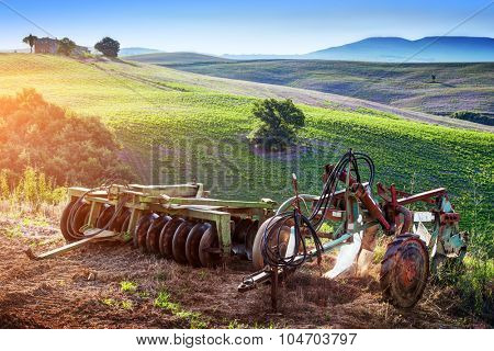 Tuscany landscape at sunrise. Retro, old agriculture machines on Tuscan hills. Italy
