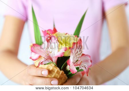 Woman holding wild flowers in wafer closeup