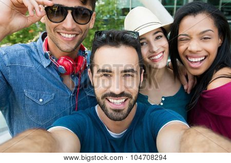 Closeup shot of young friends take a selfie. Happy smiling girls and guys photographing self. Laughing young women and men taking a photo and looking at camera.