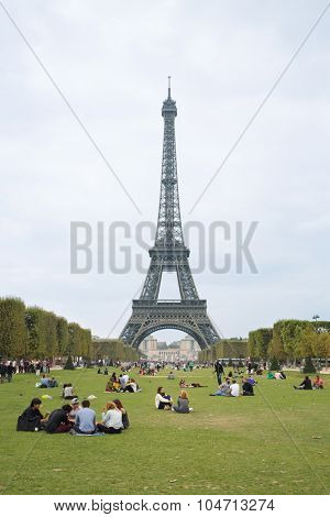 PARIS, FRANCE - SEP 11, 2014: Many tourists near the Eiffel Tower on the Champ de Mars