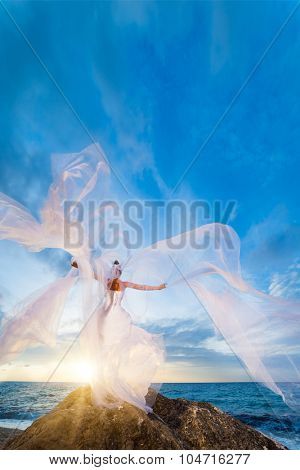 Young bride in her wedding dress at the beach at sunset