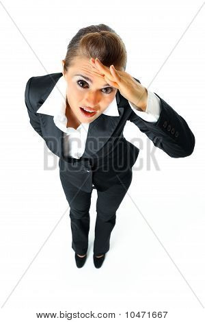 Attentive modern business woman holding hand at forehead and looking away