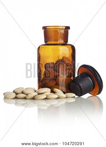 Nutritional supplement pills in and out of vintage apothecary bottle on white background