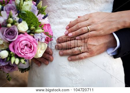 Wedding bouquet  and couple's hands with rings