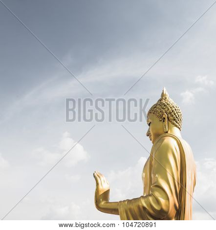 Golden Buddha Hand On 'o.k.' Sign (peace) With Blue Sky And Clouds Closeup Focused On  Hand Side Vie