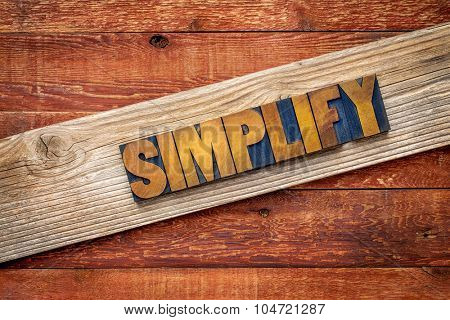 simplify word rustic sign - letterpress wood type over grained cedar plank against red barn wood