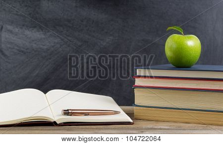 Rustic Student Desktop With Green Apple And Study Materials
