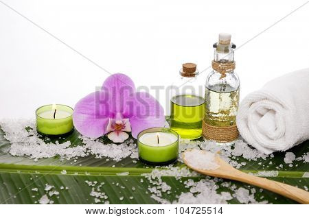 spa supplies with orchid, oil, candle , stones,salt,towel on banana leaf