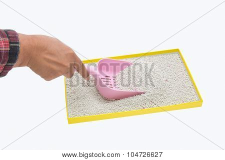 A Hand Filtering Artificial Sand With Plastic Shovel For Cat