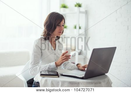 young business woman working at desk typing on a laptop in office and drinking coffee