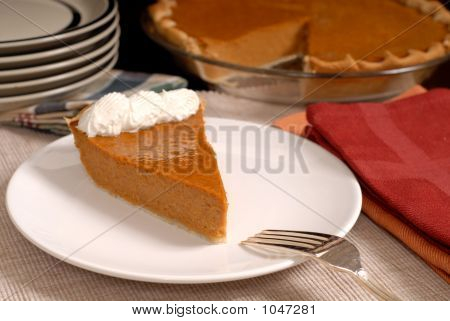 Slice Of Pumpkin Pie With Extra Plates Resting In Background Alo
