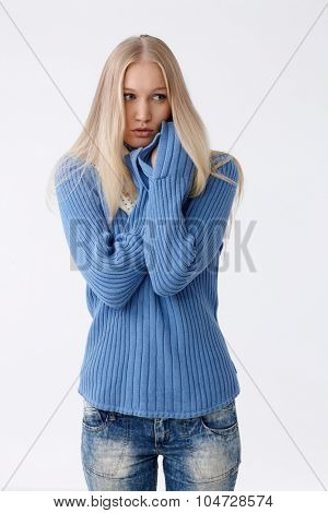 Young woman in pullover freezing or frightened, folding arms defensively, looking scared.