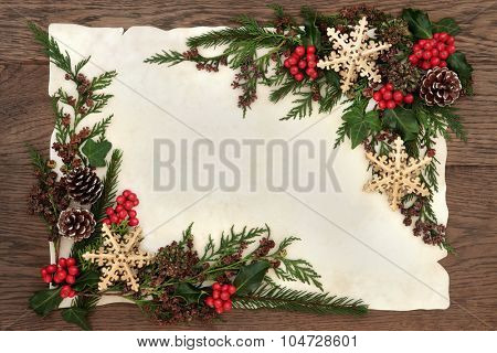 Abstract christmas border with gold snowflake decorations, holly and winter greenery on parchment paper and oak background.