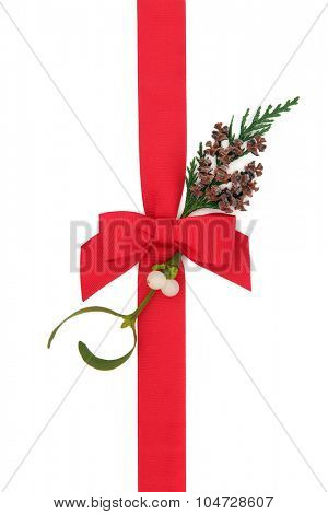 Christmas gift wrapping with red ribbon and bow, mistletoe and cedar cypress with pine cones over white background.