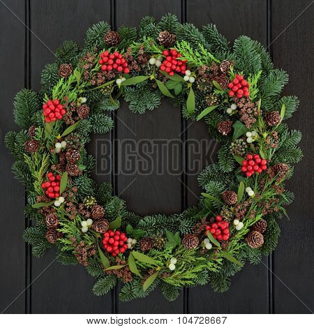 Christmas and winter wreath with holly, mistletoe, pine cones and blue spruce fir over dark blue oak  front door background.