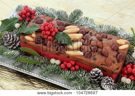 Genoa cake with holly, mistletoe and winter greenery on a silver plate over gold table cloth background.