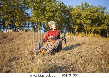Young Girl Sitting On The Grass.
