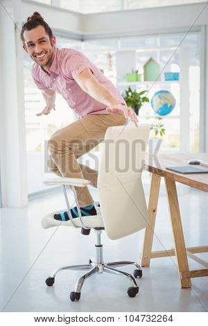 Happy businessman standing on swivel chair at desk in office