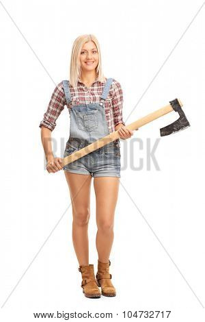 Full length portrait of a blond woman in jumpsuit and checkered shirt holding an axe and looking at the camera isolated on white background