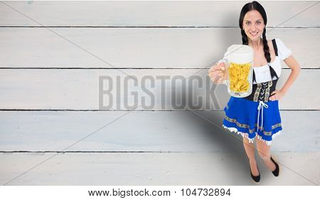 Pretty oktoberfest girl holding beer tankard against painted blue wooden planks