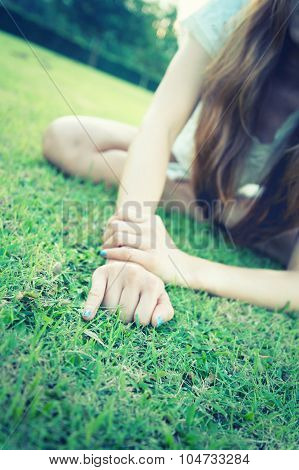 Asia Women Lying With Hand Showing Little Finger On Grass