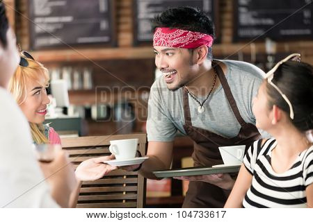 Waiter serving coffee in Asian cafe to women and man offering the drinks on a tray