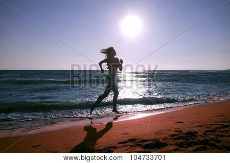 woman running on the sand at beach at sunset, full body shot, side view