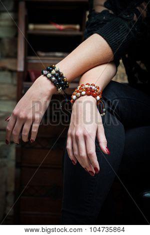 woman hands with bracelets lean on legs indoor shot closeup