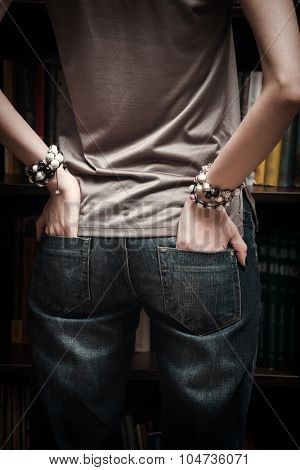 woman hands with bracelet in back pockets of the jeans indoor shot closeup