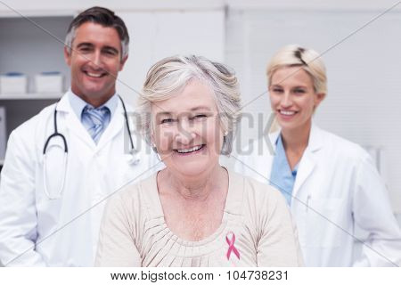 Pink awareness ribbon against senior patient smiling with doctors in clinic