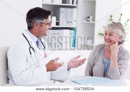 Pink awareness ribbon against doctor discussing with senior patient at table