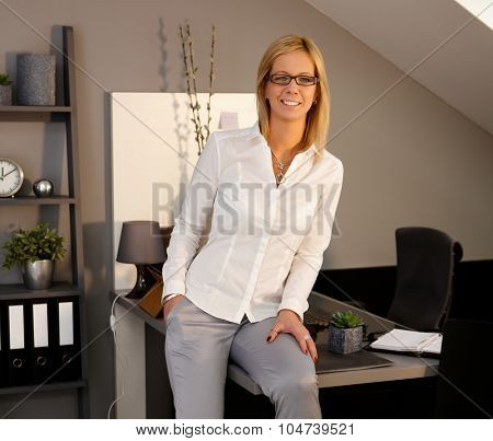 Portrait of attractive blonde businesswoman sitting on desktop in elegant office, smiling, looking at camera.