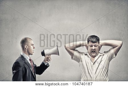 Furious man screaming agressively in megaphone at man